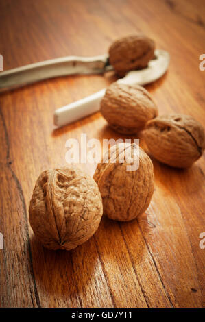 walnuts on a table with nutcracker - Stock Photo