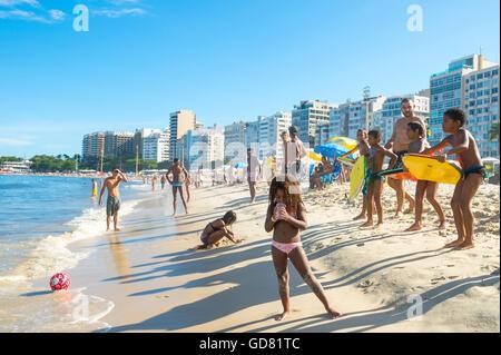 RIO DE JANEIRO - FEBRUARY 27, 2016: Brazilian children line up with bodyboards waiting for a good wave on Copacabana - Stock Photo