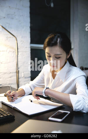 Female white-collar workers to work overtime - Stock Photo