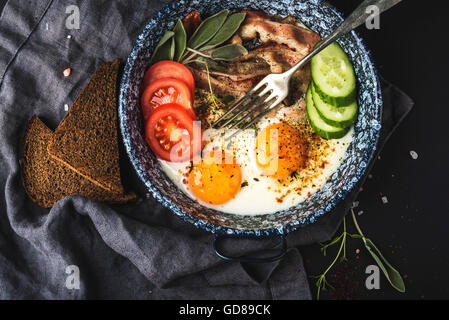 Breakfast set. Pan of fried eggs with bacon, fresh tomato, cucumber and bread over black background, top view - Stock Photo