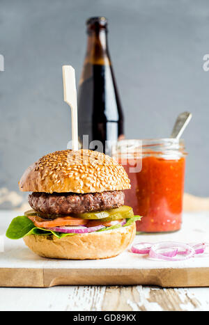Fresh homemade burger on white wooden serving board with onion rings, salsa sauce and bottle of beer over white - Stock Photo