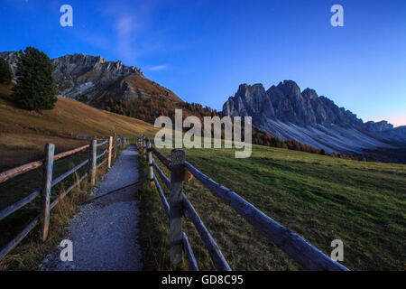 Green meadows and colorful woods in autumn frame the Odle Funes Valley South Tyrol Dolomites Italy Europe - Stock Photo