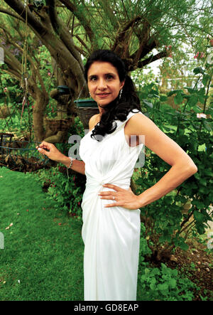Attractive young woman in smart white ballgown standing in garden prepared to go to evening function. - Stock Photo