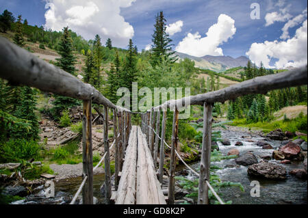 Handmade wooden pedestrian bridge over mountain stream near Telluride, CO - Stock Photo