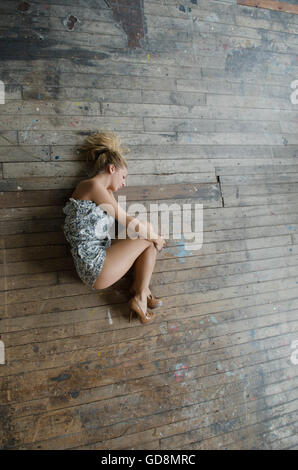 Young woman curled up on the floor - Stock Photo