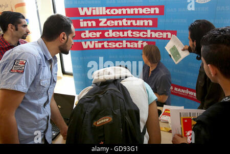 Schwerin, Germany. 14th July, 2016. People look at the stand from the Schwerin Chamber of Trade where there is a - Stock Photo