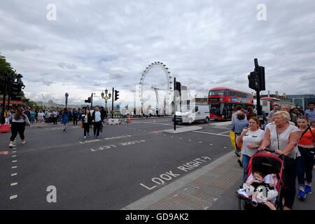 Tourists on Bridge Street City of London with the London Eye a London landmark in the background - Stock Photo