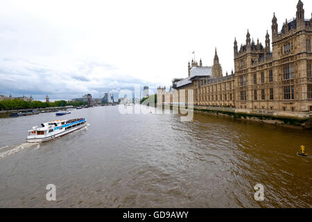A tour boat on the Thames with the Houses of Parliament a London landmark on the right - Stock Photo