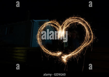 Heart drawn by sparklers using long exposure. - Stock Photo