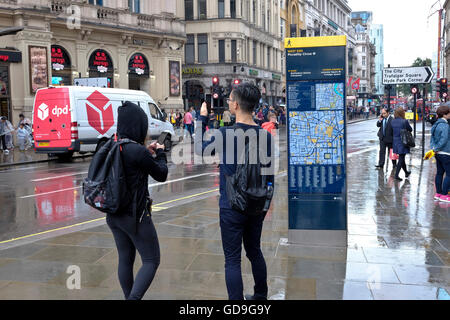 Piccadilly Circus London. A Chinese tourist takes a photograph of Eros with his smart phone on a wet and rainy day - Stock Photo