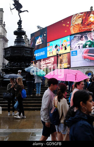 London Piccadilly Circus.The bright neon lights of the advertising displays back lighting Eros in Piccadilly Circus - Stock Photo