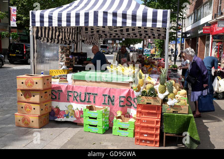 Customers buying fresh fruit from a farmers market stall set out at a flea market on a High Street in Brentwood - Stock Photo