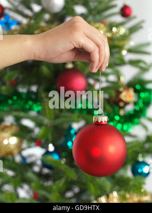 Hand holding Christmas bauble, decorating a Christmas tree - Stock Photo