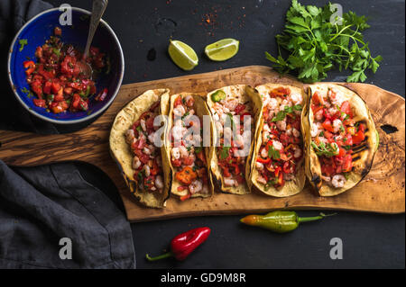 Shrimp tacos with homemade salsa sauce, limes and parsley on wooden board over dark background. Top view. Mexican - Stock Photo