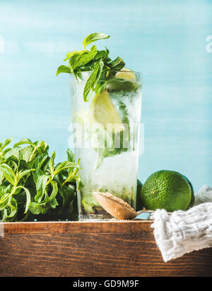 Homemade Mojito cocktail in tall glass served with bunch of mint, brown sugar and limes on wooden board. Turquoise - Stock Photo