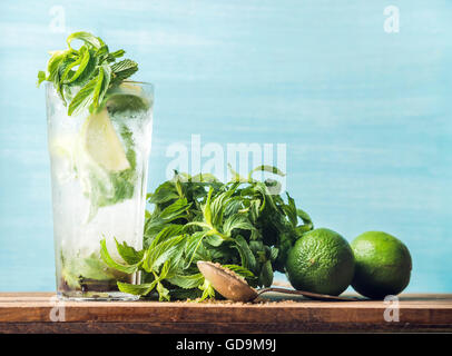 Homemade Mojito cocktail in tall glass served with bunch of mint, brown sugar and limes on wooden table. Turquoise - Stock Photo