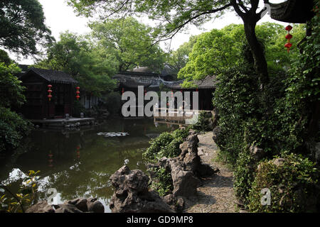 Houses, a pond, vegetation and Chinese lanterns in the Tuisi Garden, a typical old Chinese garden built in 1885. - Stock Photo