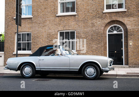 A silver classic sports car (Mercedes) shown parked in the road outside a smart residence in London. - Stock Photo