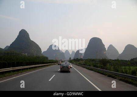 Steep karst mounds on both sides of the highway from Guilin to Yangshuo in Guangxi, this area is a very big tourist - Stock Photo