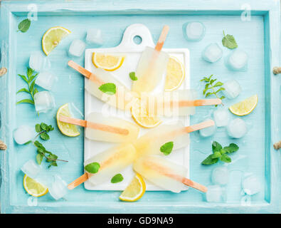 Lemon ice lollies on white ceramic board served with lemon slices, ice cubes and mint leaves over blue Turquoise - Stock Photo
