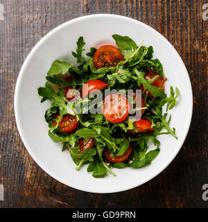 Salad with Cherry tomatoes and Arugula in white bowl on wooden background - Stock Photo