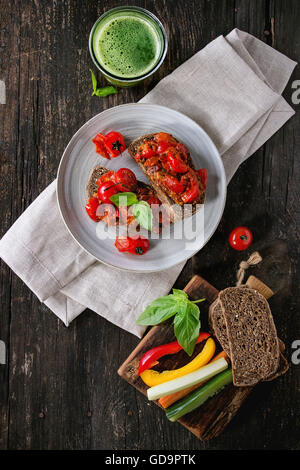 Italian tomato bruschetta with baked cherry tomatoes and sliced vegetables, served on gray ceramic plate with textile - Stock Photo