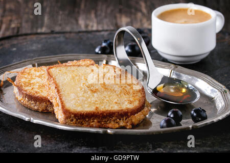 Breakfast theme. Grilled Toasts with honey, blueberries and cup of coffee espresso, served on vintage tray over - Stock Photo