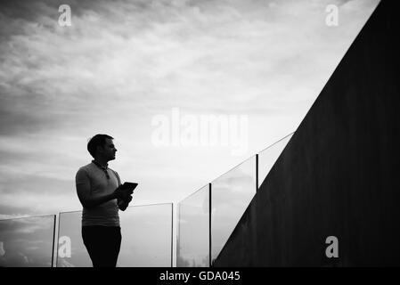 Silhouette of young business man using tablet outdoors - Stock Photo