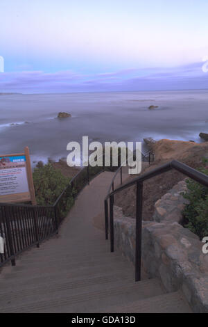 Steps from Heisler Park leading down to the sand and ocean in Laguna Beach, California at sunset. - Stock Photo