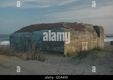 Bunkers and strong points from Hitler's Atlantic wall remains at the beach of Thyborøn. Erosion has moved or tilted - Stock Photo
