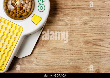 Electronic bingo game on wooden board. Horizontal image viewed from above. - Stock Photo