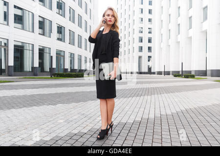 Woman full-growth in high heels with laptop and phone - Stock Photo
