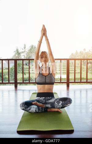 Caucasian woman practicing yoga at health center. Woman in yoga pose with eyes closed and hands joined while sitting - Stock Photo