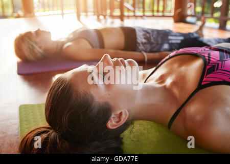 Close up shot of healthy young woman lying on floor. Young people relaxing in savasana pose at yoga class. - Stock Photo