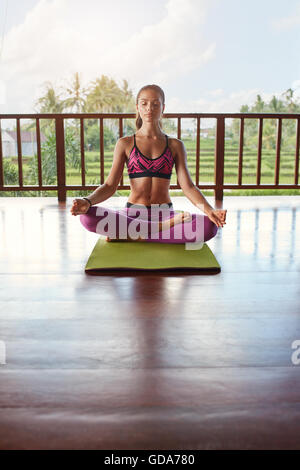 Vertical shot of female meditating in yoga class. Woman in yoga pose with eyes closed sitting on floor. - Stock Photo