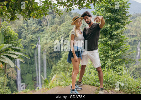 Beautiful young couple standing together on a cliff and taking selfie with waterfall. Man and woman in forest taking - Stock Photo