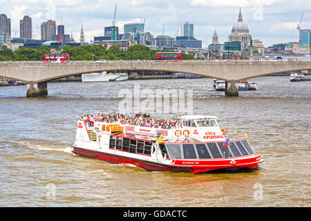 Tourists enjoying a City Cruises trip along the River Thames to take in the sights of London in July - hdr effect - Stock Photo