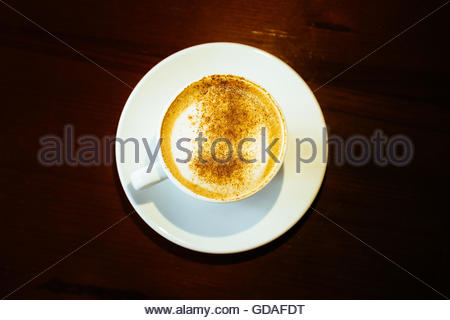 Cappuccino Coffee on Wooden table background - Stock Photo