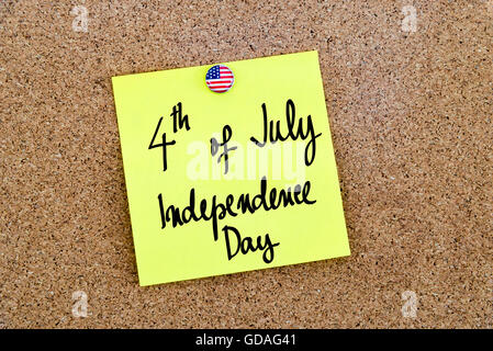 Written text 4th of July Independence Day over yellow paper note pinned on cork board - Stock Photo