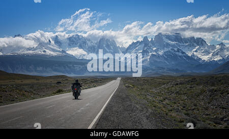 Solo motorbike rider on a lone road traveling towards snow peaked mountains in South America. - Stock Photo