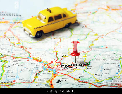 Red push pin pointing at Pamplona ,Spain  map and a taxi - Stock Photo