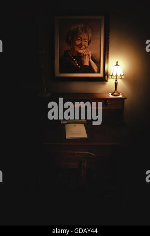 old room with a painting of the woman on the wall ,old desk and the small lamp lit in darkness - Stock Photo
