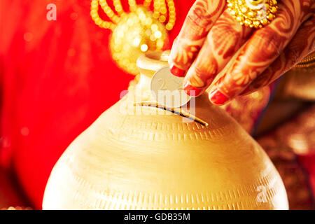 1 indian Adult Woman Bride Piggy Bank money Inserting showing - Stock Photo