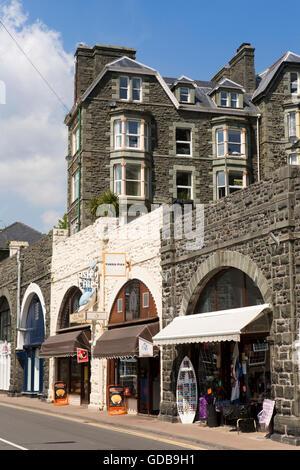 UK, Wales, Gwynedd, Barmouth, King Edward Street, shops in arches below St John's Hill - Stock Photo