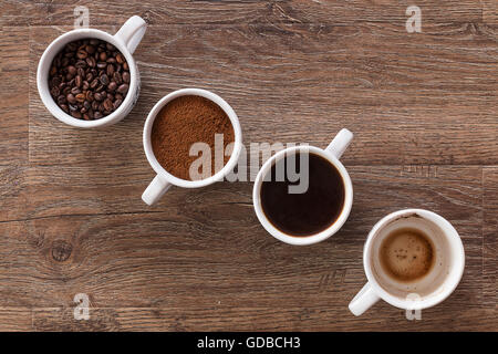 Four cups of coffee, drink phases - bean, ground and empty cup. - Stock Photo