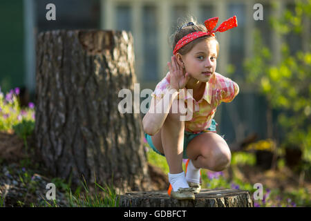 Little naughty girl outdoors, makes the gesture of listening. - Stock Photo