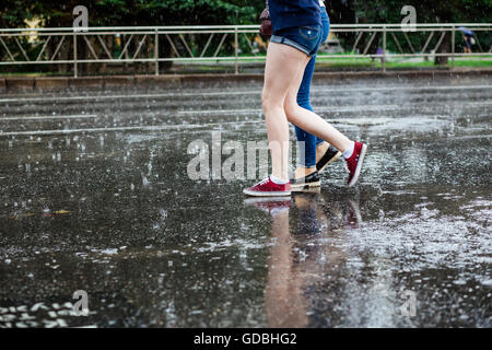 Two young women in boots crossing the street legs during heavy rain - Stock Photo