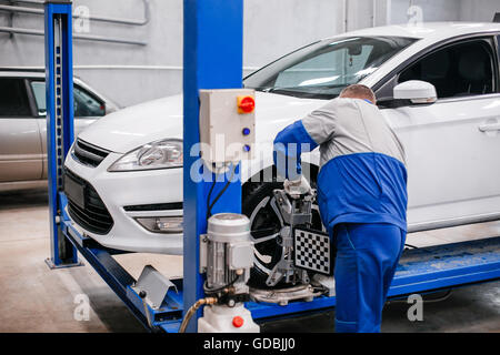 mechanic changing a wheel of a modern car in a workshop - Stock Photo