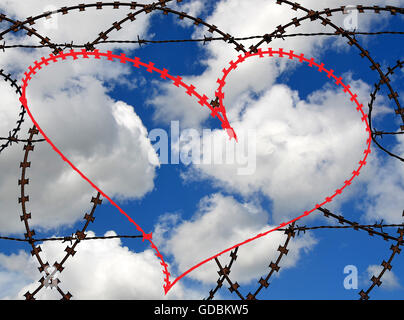 Natural heart shape (digitally coloured red) in a barbed wire fence on sky background. Love, freedom, peace, hope - Stock Photo