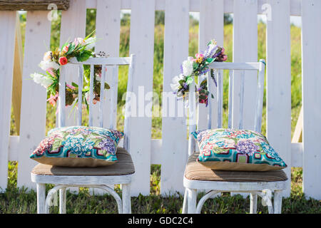 Two vintage white chairs, colorful velvet pillow and fence palisade on background decorated with flowers in boho style. Soft evening light.